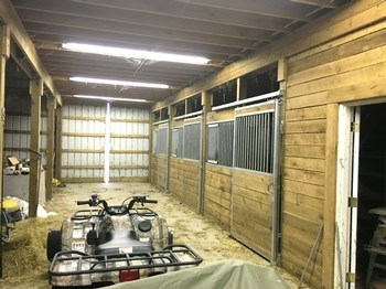 The barn has a concrete floor with three stalls. The stalls have rubber down for the horses. There is plenty more room for more stalls and it features a 200,000 BTU heating system. There is a tack room and a loft, this barn was built strong with custom made rafters. You have to see it to believe the quality. (photo 2)