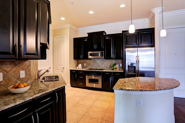 Photo is from a similar sold unit in the building. Granite counter in #303 extends in a peninsula style, no separated island. Cabinets and granite are the same. (photo 2)