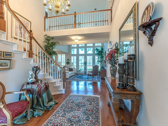 The elegant stairway and open walkway above frame the view into the formal living room at the end of the entry hall. (photo 5)