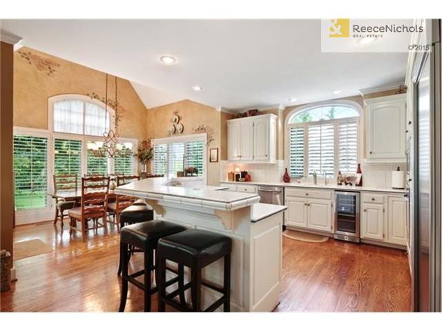 French white cabinets and large center island in the kitchen complete the heart of the home. (photo 5)