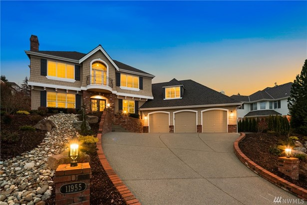 Winter twilight- Grand driveway with 3 car garage. Juliet balcony and glass entry doors.