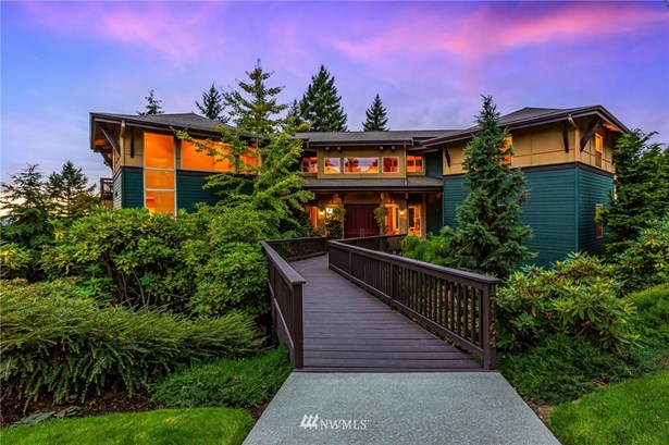 Charming bridge takes your over lush, mature landscaping as you enter the double doors into the house-no stairs to access any of the main level, including the view deck!