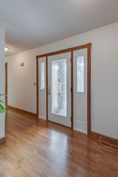 Front door entry has gleaming hardwood flooring.  Straight ahead is the living room with view of back yard.  To the right is the kitchen and family room area. (photo 5)