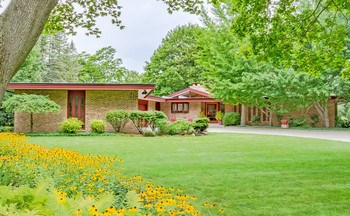 IMPECCABLY WELL KEPT MID CENTURY MODERN!! This home has been officially entered into the mid century modern database in MIdland.   Additional 2300 square feet in walkout above ground living space.  Walking distance to hospital, rail trail and downtown!!  Gorgeous perennials,  backs up to park, Sub-zero/Wolf appliances, updated kitchen and baths, sauna, steam shower, newer roof, driveway and heated garage.  ONE OF A KIND!!!  No water in this house in either flood and not located in the flood plain. (photo 1)