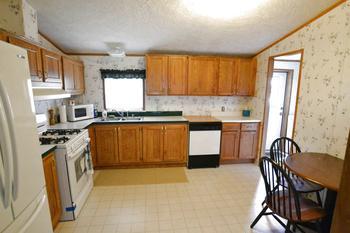 The eat in kitchen has Oak cabinets and will come with the appliances.  It is open to the living room and has easy access to the laundry room. (photo 4)