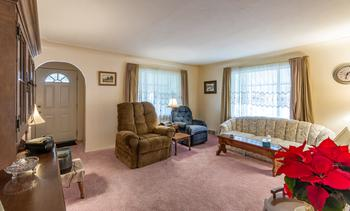 View of the living room, two large windows bring in loads of natural light. (photo 2)