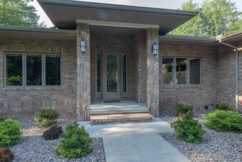 Greet your guests here at this lovely front entrance which features custom-glass doors (photo 2)
