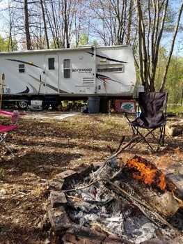 Ready for camping season?  This 7 acre parcel includes a 32ft Rockwood travel trailer and an additional pop-up camper!! Being just steps away from both state land and Wixom Lake, this location offers all of the amenities you've been searching for.  Features include underground electric and hook-up for a camper, a cleared circle drive, building site and a private storage shed.  The abundance of wildlife and excellent mix of mature trees, creates the perfect setting for deer camp.  The Rockwood travel trailer features a slide out, bathroom, kitchen and plenty of room for your family the friends! (photo 1)