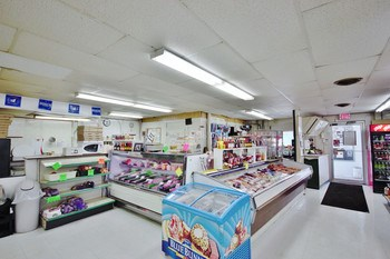 The smell of pizza welcomes customers in. A various array of fresh meats and deli items displayed in the large refrigerated cases are one of the markets many draws. (photo 5)