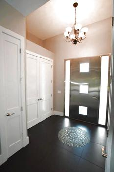 A grand entrance with high ceilings and chandelier allow focus to remain on the statement the interior of the stainless steel door demands.  An abundance of coat/storage closets are readily available to accommodate any numbers of guests! (photo 3)