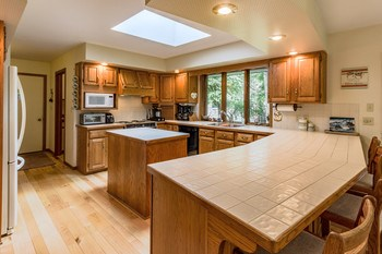 Loads of counter space plus a central island provide room for every cook.  The skylight shines daylight over the island plus great views  from the kitchen windows. (photo 3)