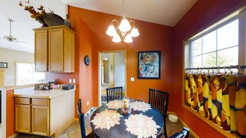 Kitchen has oak cabinets with newer title floor. Great little sitting area for morning breakfast and coffee. Nice natural light and vaulted ceilings. (photo 2)