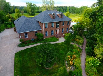 Your own private retreat- just minutes from the city!   Eight and a half acres with outdoor activities for everyone.  This Larkin Township property features almost 4000 square feet, 5 bedrooms-including a huge main floor master, a cook's delight kitchen, a temperature controlled wine room, inground pool, pond with waterfalls, your own practice golf area, and a 30x40 pole building to hold all the equipment.  The original home was built in 1999 and the main floor master and kitchen addition was added in 2009. (photo 1)