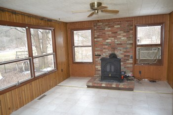 The Family room is off to the far side of the kitchen.  It features a wood burning stove and has plenty of natural light with its many windows.  There is also a door to easily access the back deck area if you wish to BBQ in the summer months. (photo 4)