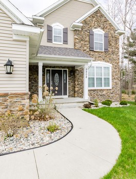 An inviting front entry and beautifully landscaped lawn welcomes you home while two stories of stacked stone exterior add architectural interest and are accented by multiple roof lines. (photo 2)