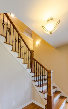 This entryway is designed to impress with its' stunning custom staircase featuring  rod iron spindles. (photo 3)