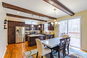 Enjoy views of the back yard from the large kitchen window, and sliding glass door that leads you onto the adjoining large deck perfectly situated for entertaining. (photo 5)