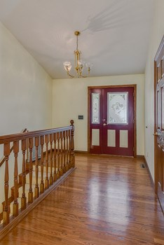 Spacious foyer with hardwood flooring and open staircase to lower level. (photo 3)