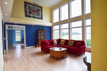 The 2-story living room provides expansive views of the lake from the first and second floors.  Super-efficient triple pane windows make sure you enjoy the views without wasting energy. (photo 5)