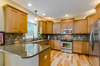 Balance. Granite and stainless steel are perfectly offset with warm cherry cabinets and rich maple flooring. (photo 4)