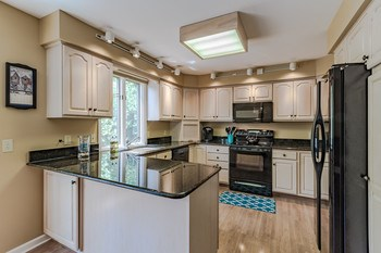 The bright, beautiful kitchen opens to the dining room and features granite counters, newer appliances, lots of cabinetry and ample counter space making meal prep a cinch. (photo 2)