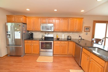 Oak cabinets, stainless steel appliances and luxury vinyl flooring (photo 2)