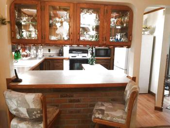 Two sided glass upper cabinets are great for displaying dishes and separate the kitchen from the living room.  Also bar seating for quick snacks. (photo 4)