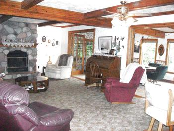 Living room has a wood burning stone fireplace and wood ceiling beams, from the foyer you can see how open of a floor plan it is. (photo 5)