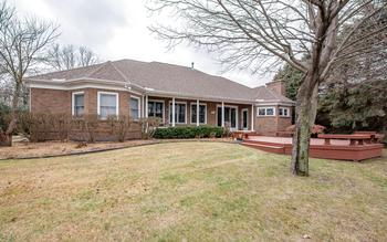All brick exterior, with covered patio and a large deck overlooking this artfully landscaped yard and the Pond. (photo 2)