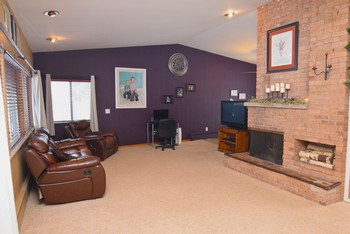 This remarkable layout and vaulted ceilings are sure to impress!  Tons of natural light and a wood burning fireplace you are sure to stay warm in the winter months. (photo 2)