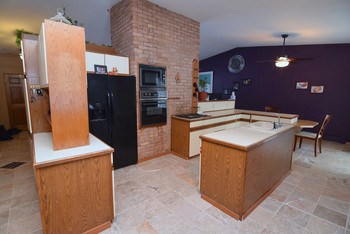 View of the spacious kitchen with vaulted ceilings, marble tiled flooring and a beautiful brick accent. (photo 3)