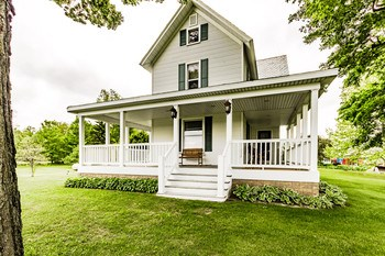 The front porch beautifully wraps around to the sides of the home giving you many different quiet places to sit and breath in the fresh country air. (photo 3)