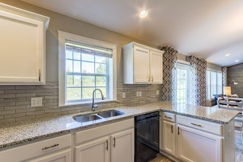 A bright white kitchen with granite countertops, tile backsplash and custom flooring is sure to be the heart of this home. (photo 5)