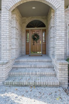 Welcome Home!   The exterior is complete brick which is maintenance free, plus there is an aggregate stone walkway greeting your guests upon arrival. (photo 2)