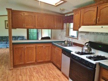 The open kitchen with space for a dining room table has all the conveniences you'll need to prepare the perfect meal. Off of the kitchen is the utility room with a washer/dryer. (photo 3)