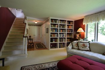 The other end of the living room includes built-in bookshelves, adjacent to the foyer. (photo 5)
