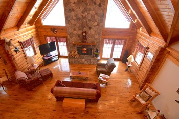 Gorgeous great room with a 2 story stone fireplace that will hold the entire family.  This room features floor to ceiling windows to enjoy all the surrounding views that this property has to offer. (photo 2)