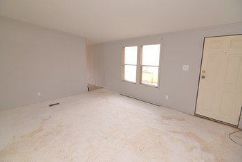 Spacious living room awaiting your choice of flooring (photo 3)