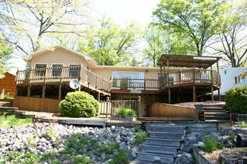 Move right in to this terrific updated ranch on Sanford Lake! With 75 ft. of water frontage, this home offers 4 bedrooms and an open floor plan concept, a newer roof (2009), beautiful hardwood floors, numerous double-french doors and windows, main floor laundry, walk-out basement, large multi-tier deck to water's edge, seawall. Most of the living space and master suite overlook the water. The main floor master has a large walk-in closet and private exit to the deck. The basement offers a cozy family room with fireplace and a 4th bedroom with e-gress window. It's location at the Southern end of Sanford Lake & proximity to US 10 makes a commute to the tri-cities fast and convenient. City water is also a bonus here. So much to offer, call today! (photo 1)