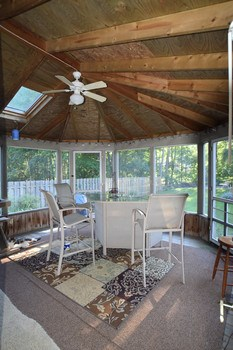 The screened in back porch features a vaulted ceiling with a ceiling fan.  A fun place to kick back and relax while enjoying the view of the backyard.  The fan keeps the space cool on those warm summer days.  A door opens to the patio off to one side making barbequing a snap. (photo 5)