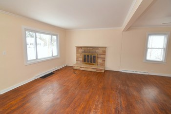 Oak floors and an open floor plan in this living room/dining room area (photo 2)