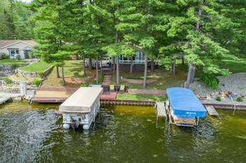 A view from the sky shows the steel seawall and the abundant lake frontage that can accommodate two docks!  (One stays and one will go.)  The trees add to the privacy of the lot without inhibiting the full lake view of the sport section of Secord Lake! (photo 2)