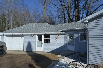 To the rear of the home is the breezeway and garage area.  The home has newer vinyl siding for easy maintenance and the roof was also installed not long ago. (photo 4)