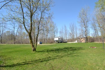 The backyard extends into a second lot next to the main.  It has a separate drive, a 14x70 cement pad. electrical hook up and the well and septic is ready for another home to be installed.  You could keep the space and add a pole barn or divide it off for another home. (photo 5)