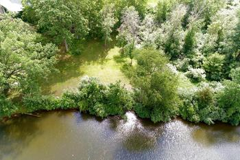 Wonderful building site nestled in a private, peaceful area with over 100 feet of river frontage.  This property is located just outside of Edenville and connects to one of Midland's county parks plus has all the perks of being close to Sanford Lake.  You can enjoy nature trails, fishing, boating, kayaking and more from this site.  The lot is large enough for your home plus a nice outbuilding and provides a gentle slope towards the water which is perfect for a walk-out basement.  You'll love the setting and there is natural gas available at this location.   Recent survey is available.   Call today for the details and restrictions! (photo 1)