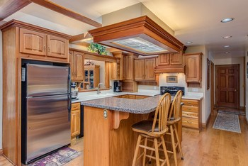 Fabulous kitchen with lots of workspace - has a pass-through opening to the formal Dining Room, features a new gas stove, stainless refrigerator, microwave and dishwasher - separate island with seating and maple floors. (photo 2)
