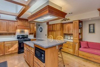 Look at all the storage - cherry cabinetry is featured and there's a cozy seating area which is a great place to store all the cookbooks and pick out your favorite recipe for dinner. (photo 3)