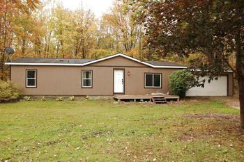 Very Private Country Setting located on 10 Wooded Acres in Glendale Township with Bullock Creek Schools. 3 Bedrooms, 2 Full Baths. Nice Manufactured Home on a Block Foundation with 2 Car Attached Garage. 1288 Sq. Ft. Open Floorplan, Some updated Windows, Floors, Fresh Paint, Water Softener & Central Air. New Carpet is being installed in the Living room, Hall & One Bedroom.  It's a Great Place to Start Out! (photo 1)