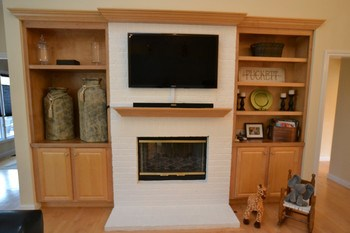 The great room has built in cabinets to display prized possessions and storage for your media.  The fireplace is a gas unit and is double sided.  You can enjoy the crackling fire from both the great room and the kitchen/dining spaces. (photo 5)