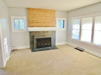 The living room offers plenty of natural light, neutral colors and a gorgeous fireplace and mantle that bring out the character of the home. (photo 2)